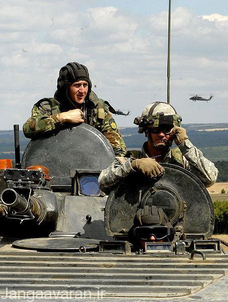 یک سرباز امریکایی در جایگاه فرمانده بی ام پی 1 ارتش رومانی در عراق . در این تصویر سر راننده و توپی که از برجک بیرون امده دیده میشود