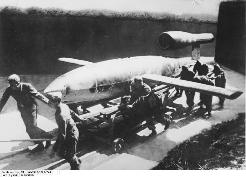 """V1 vor dem Start Aus guter Deckung wird """"V1"""" an die Abschußstelle gerollt. Der Start erfolgt durch eine Pressluftanlage. Mit Hilfe eines Fernlenkverfahrens trifft die """"V1"""" das befohlene Ziel. Die gleichbleibend hohe Geschwindigkeit, die von keinem Feindjäger erreicht wird, erhält """"V1"""" von einem Raketenantrieb. Diese erste deutsche Vergeltungswaffe ist eine hervorragende Schöpfung unserer Luftrüstung."""